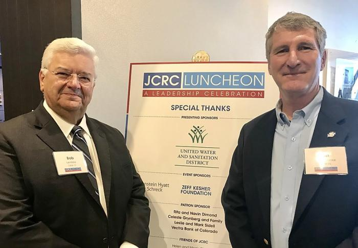 Bob Lembke, President of United Water and Sanitation District, and Ron vonLembke, Chief of Staff of United Water, pose in front of the JCRC Sponsorship Recognition Banner. United Water and Sanitation District and Bob Lembke, personally, helped sponsor the luncheon. (Photo by Lynn Bartels)